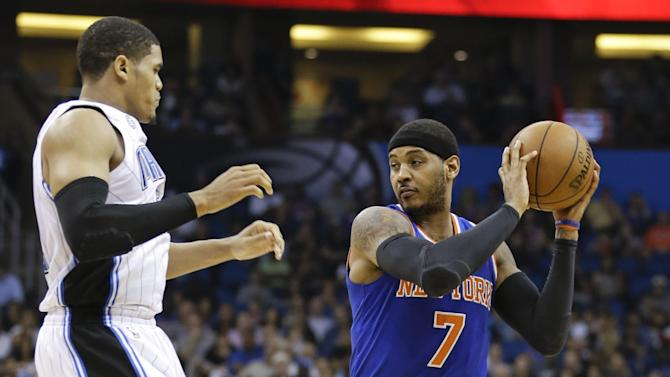 New York Knicks' Carmelo Anthony (7) looks to pass the ball around Orlando Magic's Tobias Harris, left, in the first half of an NBA basketball game in Orlando, Fla., Monday, Dec. 23, 2013