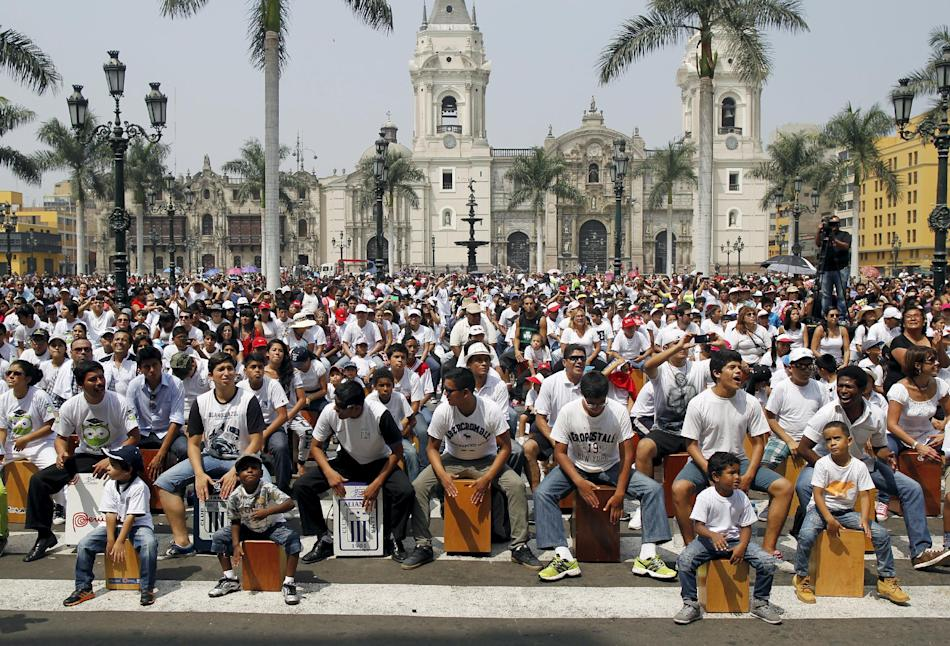 Participants play their cajones, a popular Peruvian instrument, during the 8th International Festival of the Peruvian Cajon in Lima's Plaza Mayor