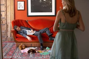 Man on sofa surrounded by mess, woman standing in background