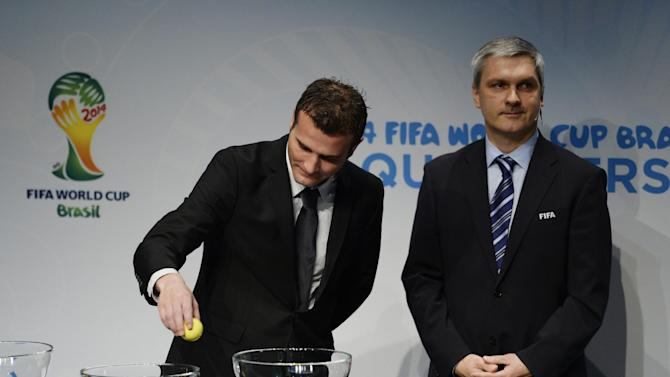 Former Swiss soccer player Alexander Frei, left, and Gordon Savic, right, Head of FIFA World Cup Qualifiers, proceed with the draw for the 2014 FIFA World Cup European zone play-off matches on Monday, Oct. 21, 2013, at the FIFA headquarters in Zurich, Switzerland