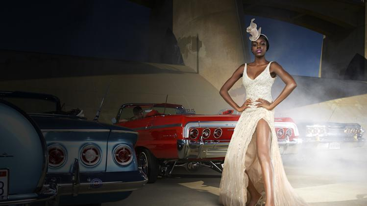 "Alisha models a British couture hat while posing with a vintage American car on ""America's Next Top Model."""