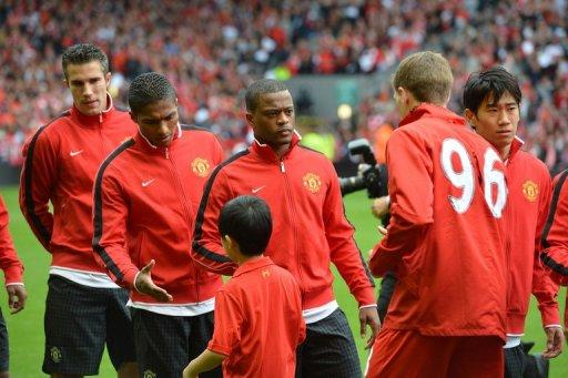 Manchester United defender Patrice Evra (3rd left) waits to shakes hands with Liverpool Steven Gerrard (2nd right)