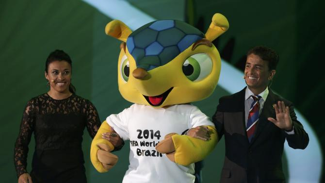 Marta and Bebeto introduce Fuleco during the draw for the 2014 World Cup in Sao Joao da Mata
