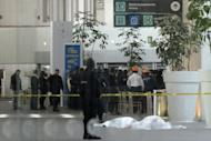 Federal police stand guard next to the bodies of two police officers shot dead in the fast-food area of Benito Juarez international airport Terminal 2, in Mexico City, on June 25, 2012