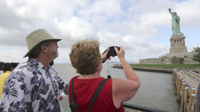 Rodney and Judy Long, of Charlotte, N.C., take a photo of the Statue of Liberty as they arrive on the first tourist ferry to leave Manhattan, Thursday, July 4, 2013, in New York. The Statue of Liberty finally reopened on the Fourth of July months after Superstorm Sandy swamped its island in New York Harbor as Americans across the country marked the holiday with fireworks and barbecues. (AP Photo/Mary Altaffer)