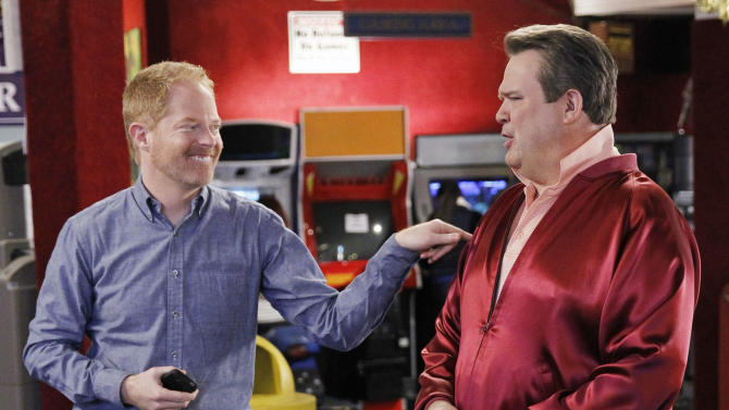 """This TV publicity image released by ABC shows Eric Stonestreet, as Cameron, right, and Jesse Tyler Ferguson as Mitchell in a scene from the comedy """"Modern Family.""""  The ACLU is lobbying for the gay couple on """"Modern Family"""" to get married. ACLU Action started a campaign to urge the show's producers to script a wedding episode for Mitchell and Cameron, already fathers of an adopted child and one of three couples at the heart of the show. (AP Photo/ABC, Peter """"Hopper"""" Stone)"""