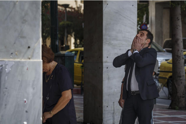 A woman, left, withdraws money from a National Bank ATM machine as a man touches his face while waiting in a queue in central Athens on in this photo dated Saturday, June 27, 2015. The latest incarnat