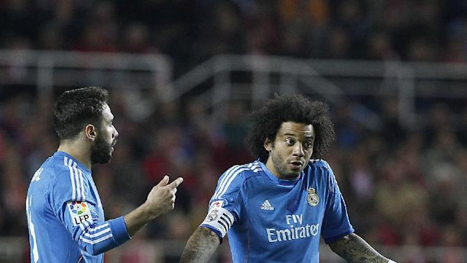 Real Madrid's Marcelo Vieira from Brazil, right and Daniel Carvajal talk during their La Liga soccer match against Sevilla  at the Ramon Sanchez Pizjuan stadium, in Seville, Spain on Wednesday, March 26, 2014