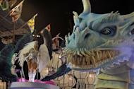 A reveler of the Inocentes de Belford-Roxo samba school performs atop a float during the first night of Carnival parade at the Sambadrome in Rio de Janeiro on February 10, 2013