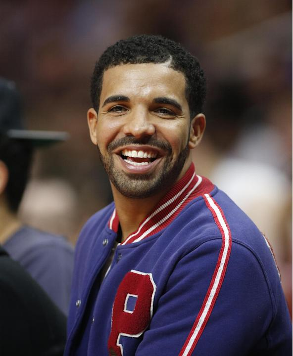 Recording artist Drake smiles as he sits courtside at the Staples Center during an NBA basketball game between the Los Angeles Clippers and Golden State Warriors, Tuesday, March 31, 2015, in Los Angel