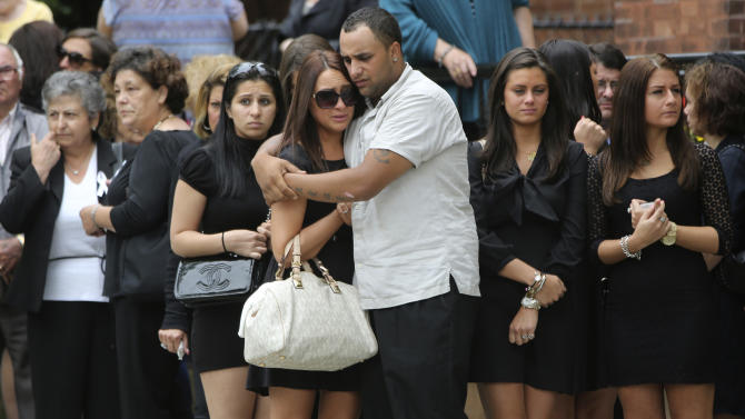 Mourners embrace outside St. Teresa of Avila Church after the funeral service for Andrea Rebello, Wednesday, May 22, 2013 in Sleepy Hollow, N.Y. Rebello, a junior at Hofstra University in Hempstead, N.Y., was shot and killed Friday, May 17, 2013, during a break-in near the college campus.  (AP Photo/Mary Altaffer)