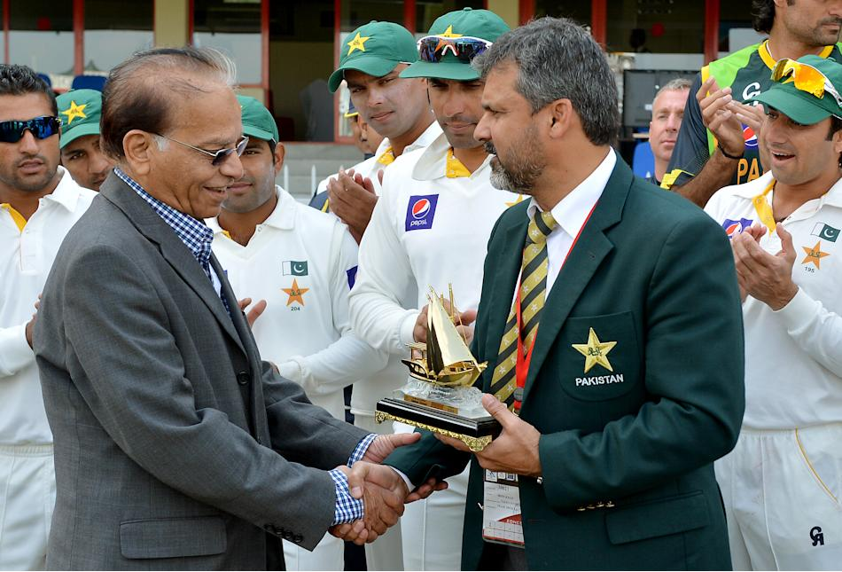 Pakistan cricket team manager Moin Khan (R) gives a present to veteran journalist Qamar Ahmed (L) during the opening day of the third and final cricket Test match between Pakistan and Sri Lanka at the