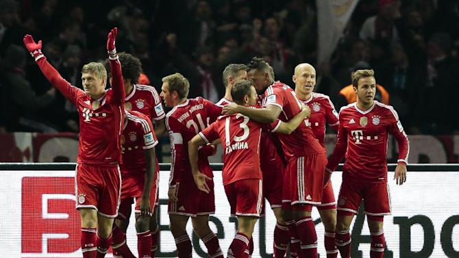 Bayern's Toni Kroos, left, celebrates with the team after scoring his side's first goal during the first division Bundesliga soccer match between Hertha BSC and FC Bayern Munich in Berlin, Tuesday, March 25, 2014. (AP Photo/Markus Schreiber)