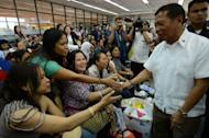 Philippine Vice-President Jejomar Binay (R) welcomes women workers, who had been working in Syria, after they disembarked from a plane chartered by the International Organization for Migration at the international airport in Manila