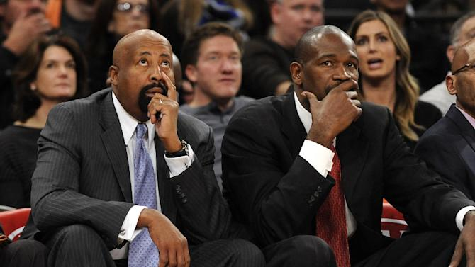 New York Knicks' head coach Mike Woodson, left, looks at the scoreboard as assistant coach Herb Williams reacts as their team falls behind the Boston Celtics during the first half of an NBA basketball game on Sunday, Dec. 8, 2013, in New York. The Celtics won 114-73