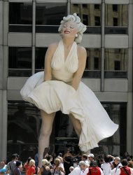 The curious gather around Seward Johnson's 26-foot-tall sculpture of Marilyn Monroe, in her most famous wind-blown pose, on Michigan Ave. Friday, July 15, 2011 in Chicago. (AP Photo/Charles Rex Arbogast)