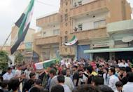 Syrians mourners, waving the pre-Baath former national flag adoped by the opposition movement, carry the coffin of Mazloum Hussein Khalil, an alleged vicitm of recent violence in the northern, mostly Kurdish region of Qamishli