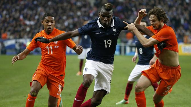 France's Pogba challenges Netherland's Boetius and Blind during their international friendly soccer match at the Stade de France in Saint-Denis