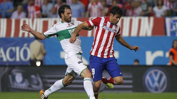 Atletico's Diego Costa, right, in action with Elche's Sergio Pelegrin, left, during a Spanish La Liga soccer match between Atletico de Madrid and Elche at the Vicente Calderon stadium in Madrid, Spain, Friday, April 18, 2014