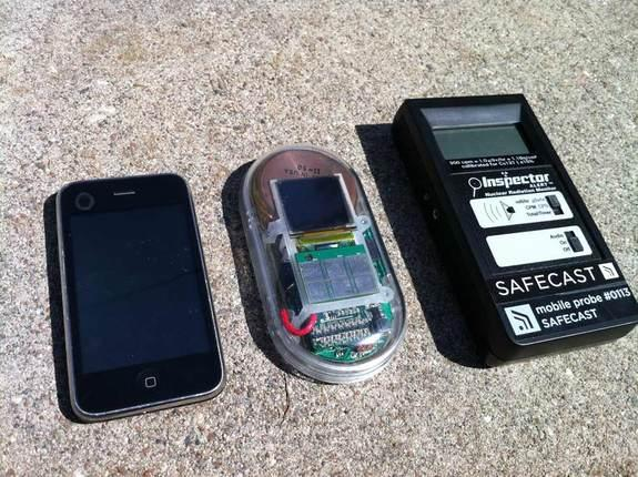 The homemade Safecast Geiger counter sits between a smartphone and a commercial Geiger counter.