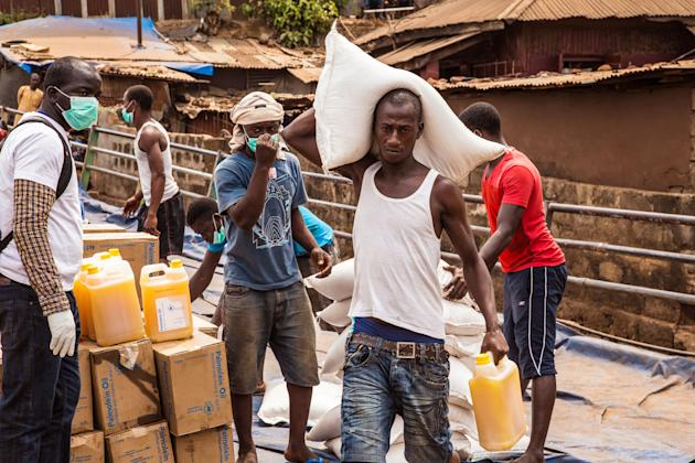 Workers carry food to be distributed to the needy as Sierra Leone enters a three day country wide lockdown on movement of people due to the Ebola virus in the city of Freetown, Sierra Leone, Friday, M