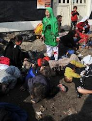 Tarana (R), 12, reacts while surrounded by the bodies of men, women and children who died after a suicide bomber detonated a bomb during a religious ceremony in Kabul in December, 2011. The photographer, Massoud Hossaini, won the prestigious Pulitzer Prize for the image