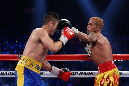 Amnat of Thailand punches Zou of China during their IBF world flyweight title fight in Macau