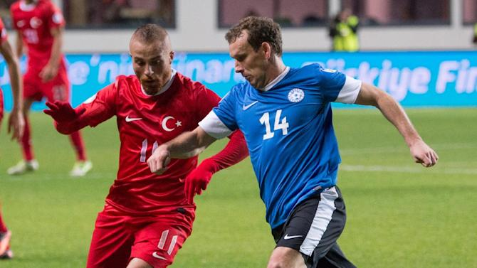 Estonia's Konstantin Vassiljev, right,  fights for the ball with Turkey's Gokhan Tore during their World Cup Group D qualifying soccer match in Tallinn, Estonia, Friday, Oct. 11, 2013