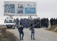 Palestinian policemen hold shields as demonstrators throw stones outside the Jalazoun refugee camp near the West Bank city of Ramallah January 12, 2014. REUTERS/Mohamad Torokman
