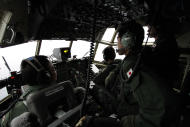Japanese Air Self-Defense Force's Capt. Junichi Tanoue, left, co-pilot Ryutaro Hamahira, second from left, and engineer Noriyuki Yamanouchi, second from right, scan the ocean aboard a C130 aircraft while it flies over the southern search area in the southeastern Indian Ocean, 200 to 300 kilometers (124 to 186 miles) south of Sumatra, Indonesia, Friday, March 21, 2014. Search planes scoured a remote patch of the Indian Ocean but came back empty-handed Friday after looking for any sign of the missing Malaysia Airlines jet, another disappointing day in one of the world's biggest aviation mysteries. (AP Photo/Koji Ueda)