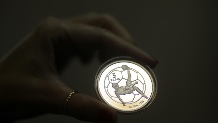 Worker from the Casa da Moeda do Brazil shows a FIFA 2014 World Cup commemorative silver coin after its production in Rio de Janeiro