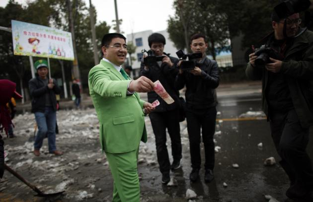 "Chinese multimillionaire Chen Guangbiao gives money away to street cleaners during an event he organised, where people representing companies, which Chen claims pollute the environment, took part in a parade to be publicly ""shamed"", in Nanjing, Jiangsu province, in this file picture taken February 21, 2013. To match Newsmaker CHINA-TIMES/ REUTERS/Carlos Barria/Files (CHINA - Tags: ENVIRONMENT BUSINESS SOCIETY)"