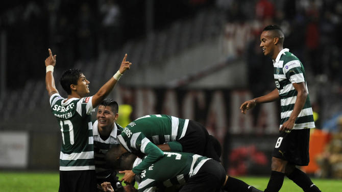 Sporting's Cedric Soares his mobbed by teammates as they celebrate scoring against Sporting Braga during their Portuguese League soccer match at the Municipal Stadium, in Braga, Portugal, Saturday Sept. 26, 2013. Cedric Soares  and Fredy Montero, left, scored the two goals in Sporting's 2-1 victory