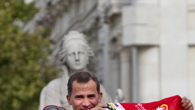 Geox-TMC team member Juan Cobo, left, gives the overall leader's signed red jersey to Spain's Crown Prince Felipe, right, during the podium ceremony after winning the Spanish Vuelta cycling in Madrid, Spain, Sunday, Sept. 11, 2011. (AP Photo/Arturo Rodriguez)