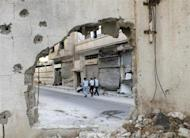 Men walking along a road are seen through a hole in a wall in the besieged area of Homs September 19, 2013. REUTERS/Yazan Homsy