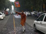 A supporter of India's main opposition Bharatiya Janata Party (BJP) waves the party's flag during celebrations before India's Hindu nationalist Narendra Modi was crowned as the prime ministerial candidate for the BJP outside the party headquarters in New Delhi September 13, 2013. REUTERS/Ahmad Masood