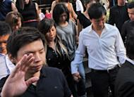 Pastor Kong Hee (in white shirt) holds his wife Ho Yeow Sun's hand as they leave court in Singapore on June 27, 2012. The founder of one of Singapore's richest churches was arrested on June 26, on allegations of misusing at least 18 million USD in donations from his congregation of more than 30,000 to support his wife's singing career, police said