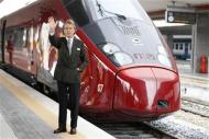 "Luca Cordero di Montezemolo, president for the NTV, waves as he poses in front of the new high-speed train ""Italo"" at the Naples central station"