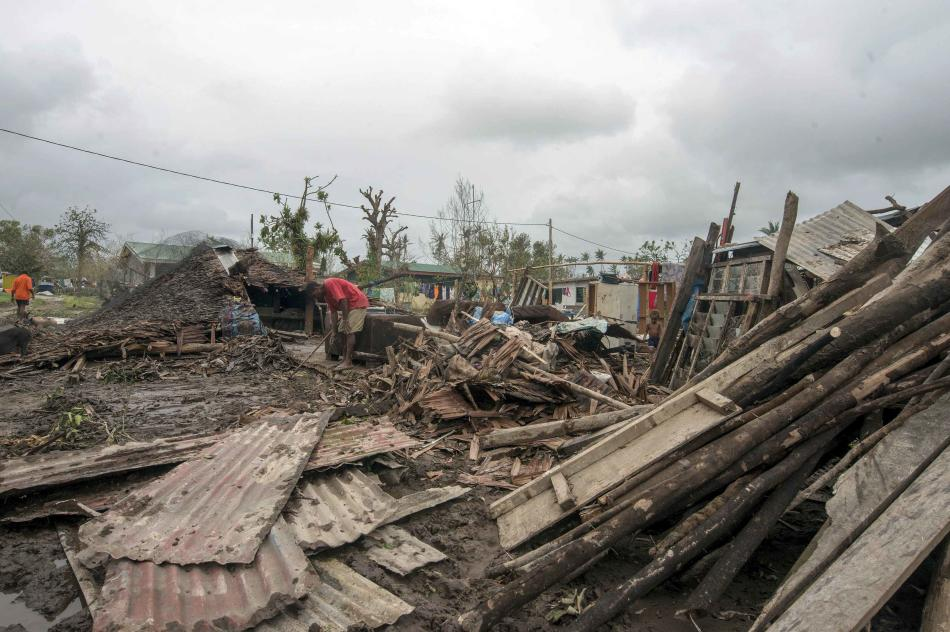 Local residents move debris near their homes destroyed by Cyclone Pam in Port Vila, the capital city of the Pacific island nation of Vanuatu