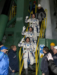 Expedition 39 Soyuz Commander Alexander Skvortsov of the Russian Federal Space Agency, Roscosmos, bottom, Flight Engineer Steve Swanson of NASA, middle, and Flight Engineer Oleg Artemyev of Roscosmos, wave farewell prior to boarding the Soyuz T
