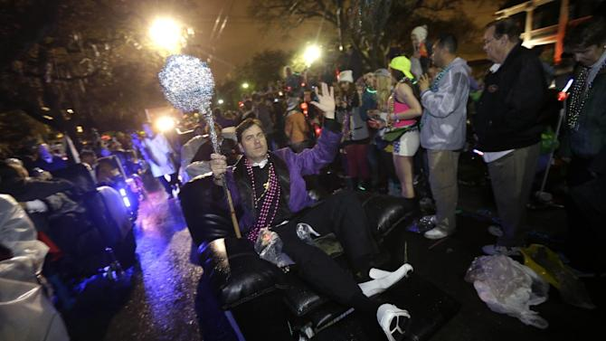 Members of the Laissez Boys Pleasure Aid &Leisure Club parade in motorized easy chairs during the Krewe of Orpheus Mardi Gras parade in New Orleans, Monday, Feb. 11, 2013. (AP Photo/Gerald Herbert)