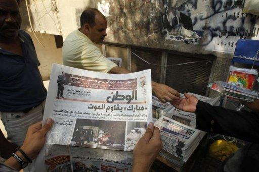Egyptians read local newspapers with front page news on the health situation of ousted president Hosni Mubarak