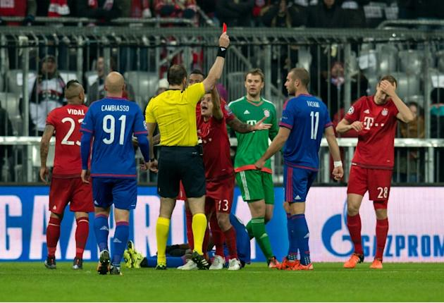 """Referree Jonas Eriksson shows a red card to Bayern Munich's Holger Badstuber (R) during a UEFA Champions League match against Olympiakos on November 24, 2015 at the """"Allianz Arena"""" in Mu"""