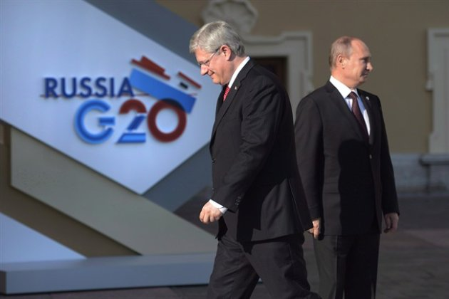 Canadian Prime Minister Stephen Harper walks past Russian President Vladimir Putin at the G20 Summit.