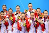 China's team celebrate on the podium after winning silver in the team free routine final during the synchronised swimming competition at the London 2012 Olympic Games, on August 10, in London
