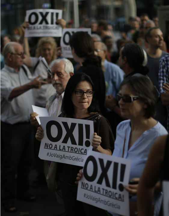 People protest during a pro Greece demonstration at the European Union office in Barcelona, Spain, Friday, July 3, 2015 . A new opinion poll shows a dead heat in Greece's referendum campaign with