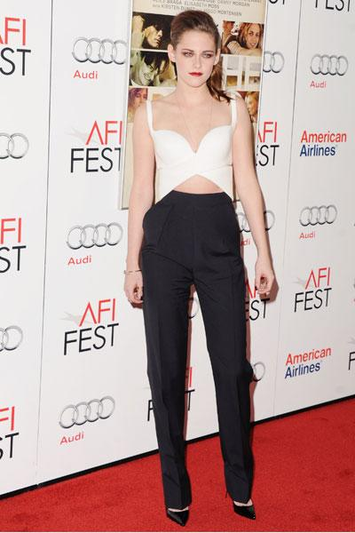 Kristen Stewart shows us once again that she is willing to take fashion risks in this daring ensemble featuring a low-cut, criss-cross crop top and high-waisted cigarette trousers. The 22-year-old wor