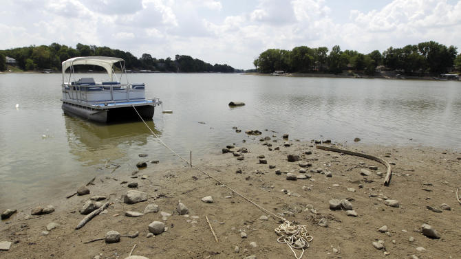 A pontoon is anchored on a mud flat as the owner could not reach their dock at Morse Reservoir in Noblesville, Ind., Monday, July 16, 2012. The reservoir is down nearly 6 feet from normal levels and being lowered 1 foot every five days to provide water for Indianapolis. The nation's widest drought in decades is spreading, with more than half of the continental United States now in some stage of drought and most of the rest enduring abnormally dry conditions. (AP Photo/Michael Conroy)
