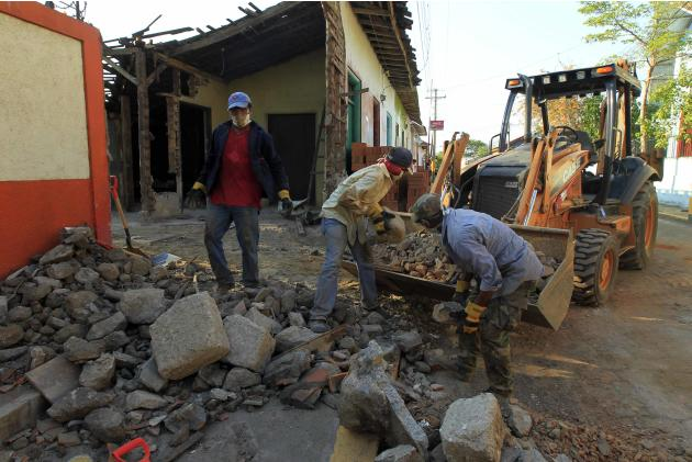 Employees of the Mayor's office remove debris from a home that was destroyed during a strong earthquake that struck last week, in Managua