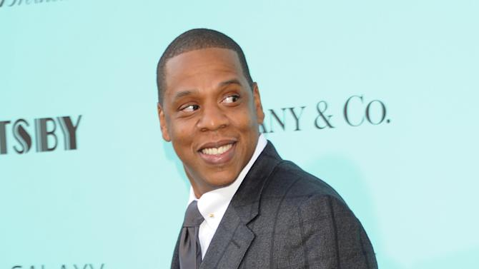 """FILE - This May 1, 2013 file photo shows Jay-Z at """"The Great Gatsby"""" world premiere at Avery Fisher Hall in New York. Jay-Z is teaming up with Samsung to release his new album, unveiling a three-minute commercial during the NBA Finals and announcing a deal that will give the music to 1 million users of Galaxy mobile phones. The new album, called """"Magna Carta Holy Grail,"""" will be free for the first 1 million android phone owners who download an app for the album. Those who do so will get the album on July 4, three days before its official release. (Photo by Evan Agostini/Invision/AP, file )"""